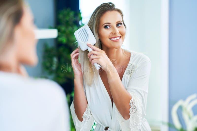 Happy woman brushing hair in bathroom. Adult woman brushing her hair in bathroom royalty free stock images
