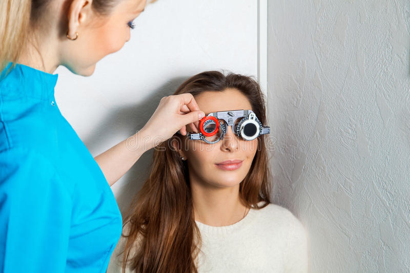 Adult woman checks vision in an ophthalmologist with corrective. Adult women checks vision in an ophthalmologist with corrective lenses. Ophthalmologist. medical stock photo