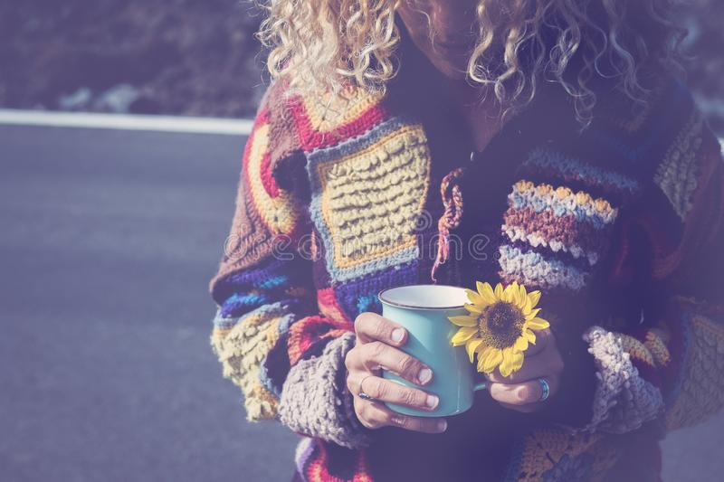 Adult woman with cup of coffee and yellow sun flower with road in backgrund - concept of travel and independence for free people. Outdoor stock image