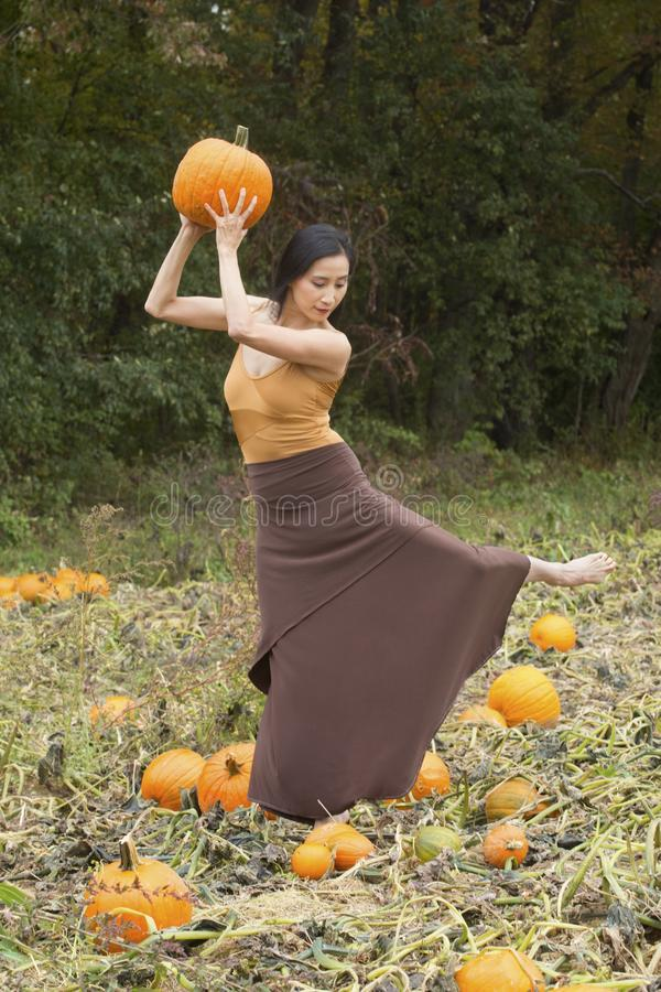 Adult woman dancing with pumpkins on a farm in Connecticut royalty free stock photo