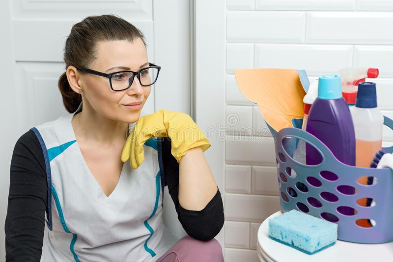 Adult woman doing cleaning with detergents. Woman in glasses, professional uniform in bathroom, toilets room stock photos