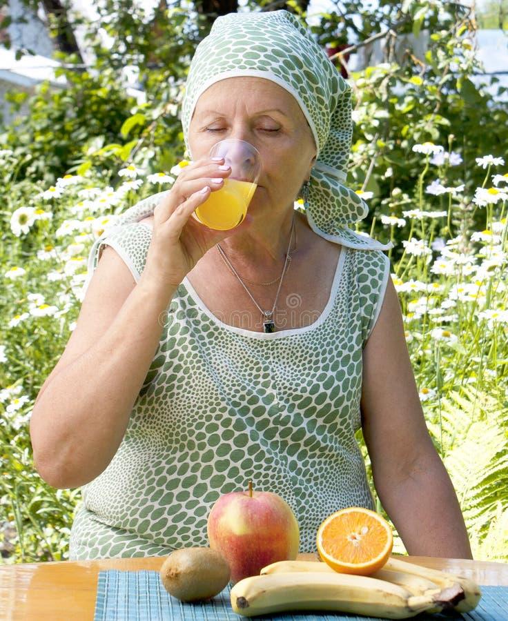 The  adult woman drinks fresh orange juice
