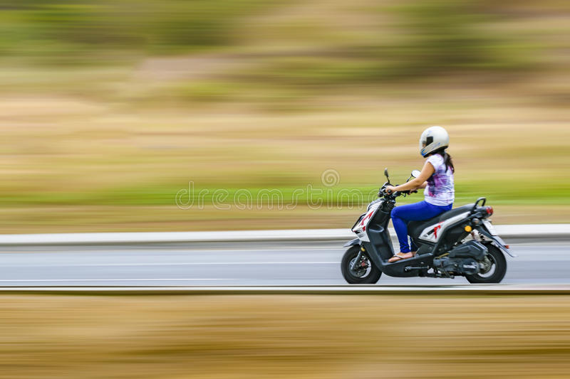 Adult Woman Driving Scooter at Outdoor stock images