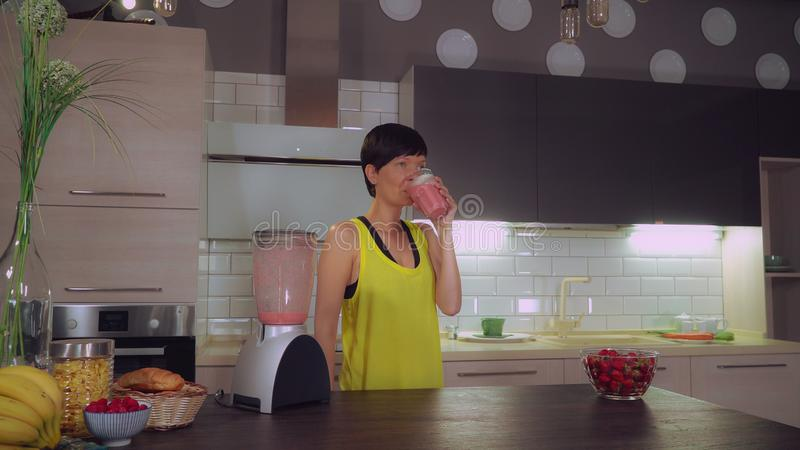 Brunette drinks juice in flat. Adult woman entering in kitchen after workout drinking fruit smoothie. Female wearing yellow sportswear relish healthy drink at stock images