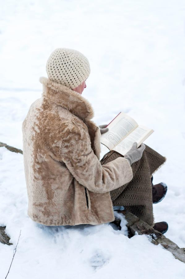 Woman ready a book in winter royalty free stock image