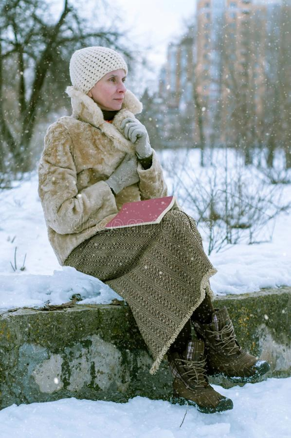 Woman ready a book in winter stock photography