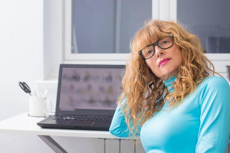 Adult woman with glasses and computer royalty free stock photography