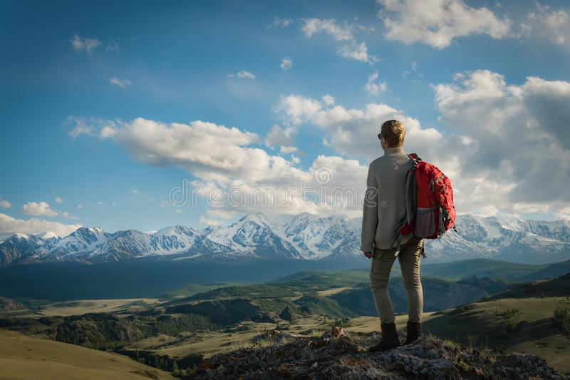 Adult woman hiker stands on the top enjoys mountain views stock image