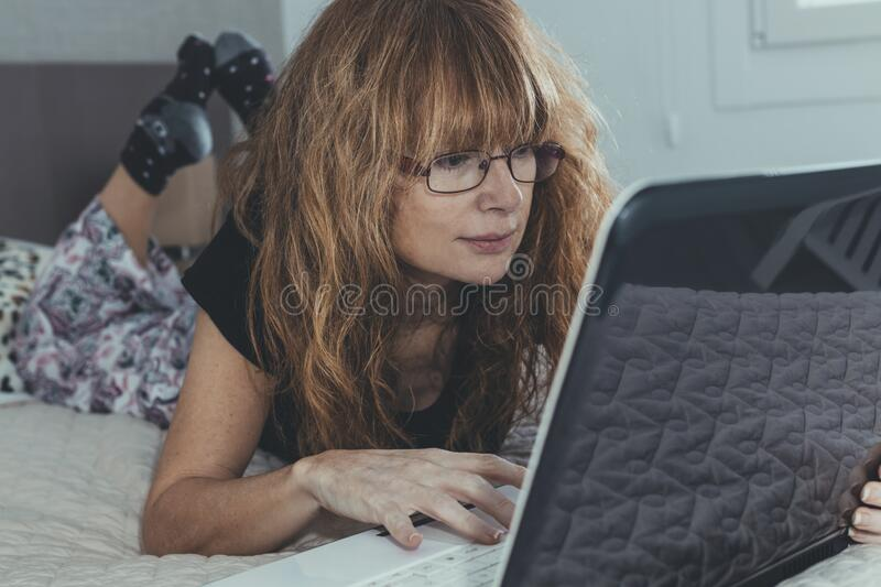 Woman with laptop in the room or bedroom. Adult woman with laptop in the room or bedroom stock image