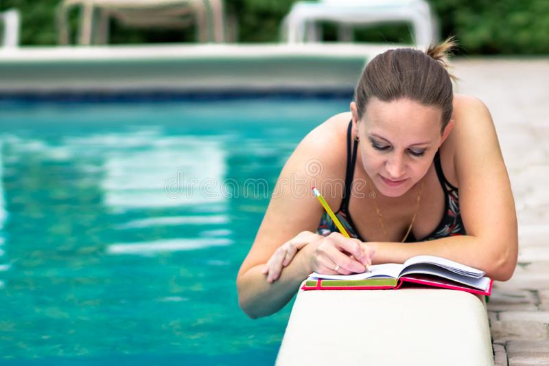 Adult woman laying on a pool and writes in a notebook in beautiful sunny day stock image