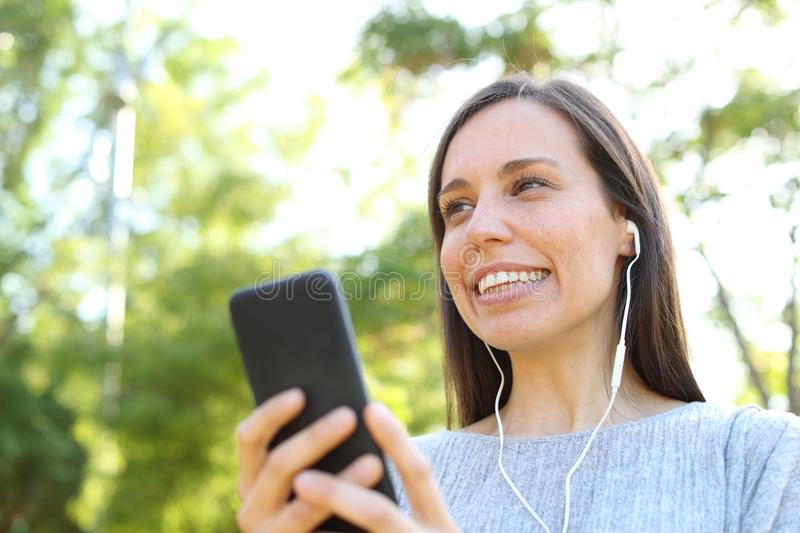 Adult woman listening to music in a park stock photos