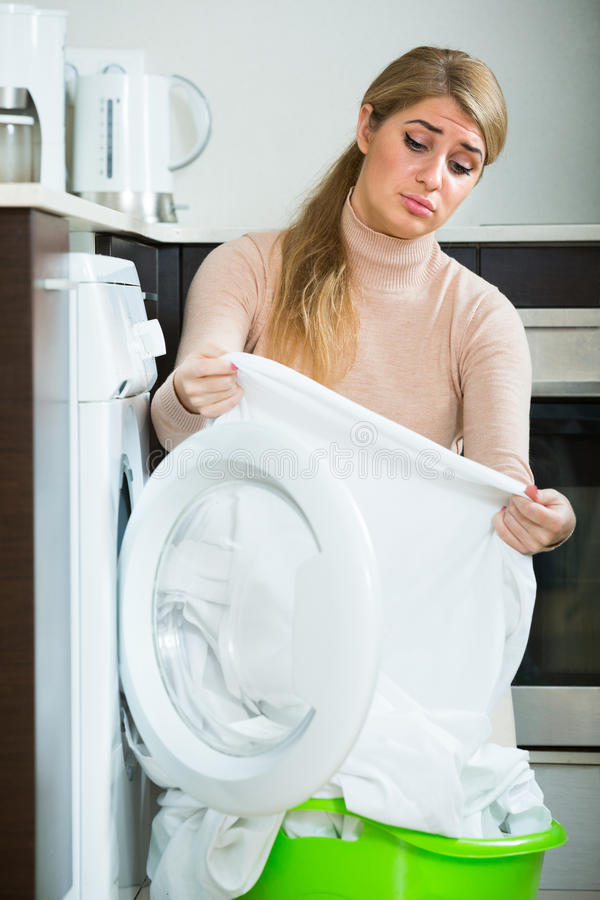 Adult woman with musty linen. Woman displeased with quality of washing linen after laundry at home stock photography