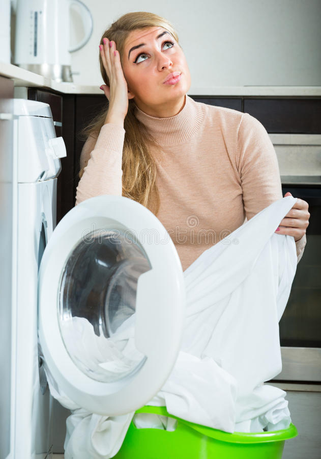 Adult woman with musty linen. Housewife displeased with washing quality of linen after laundry at home stock photos