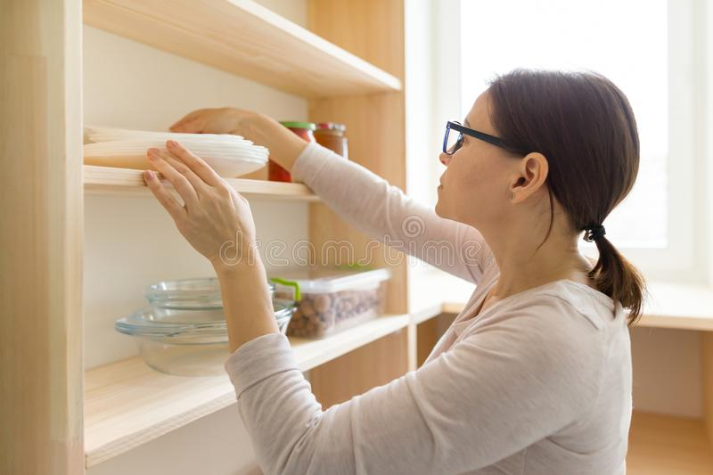 Adult woman picking food from storage cabinet in kitchen, storage with wooden shelves royalty free stock photos