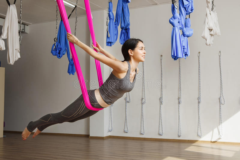 Adult woman practices inversion anti-gravity yoga position in gym. Aerial antigravity yoga girl on pink silk hammock, doing exercises, meditating in calm stock photos