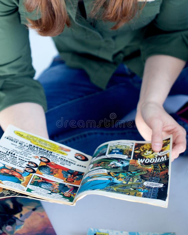 Adult woman reading comics books. Close up of a grown up woman reads some comics royalty free stock photos