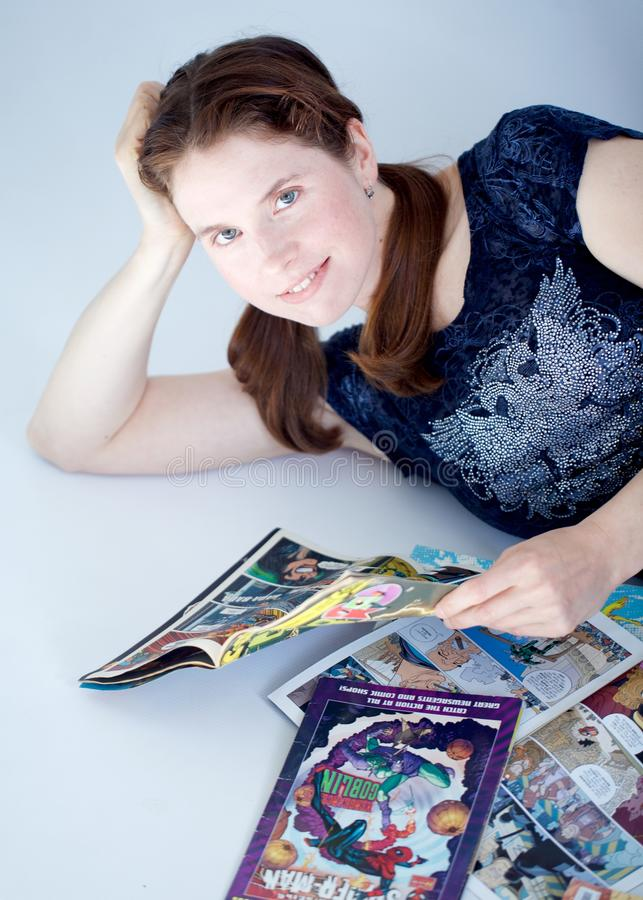 Adult woman reading comics books. A smiling pretty grown up woman reads some comic book laying down royalty free stock photos