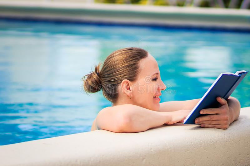 Adult woman reading interesting book in a pool in beautiful sunny day royalty free stock images