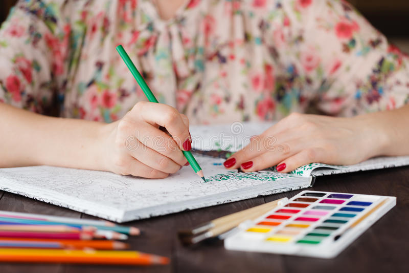 Adult woman relax by paining coloring book stock photo