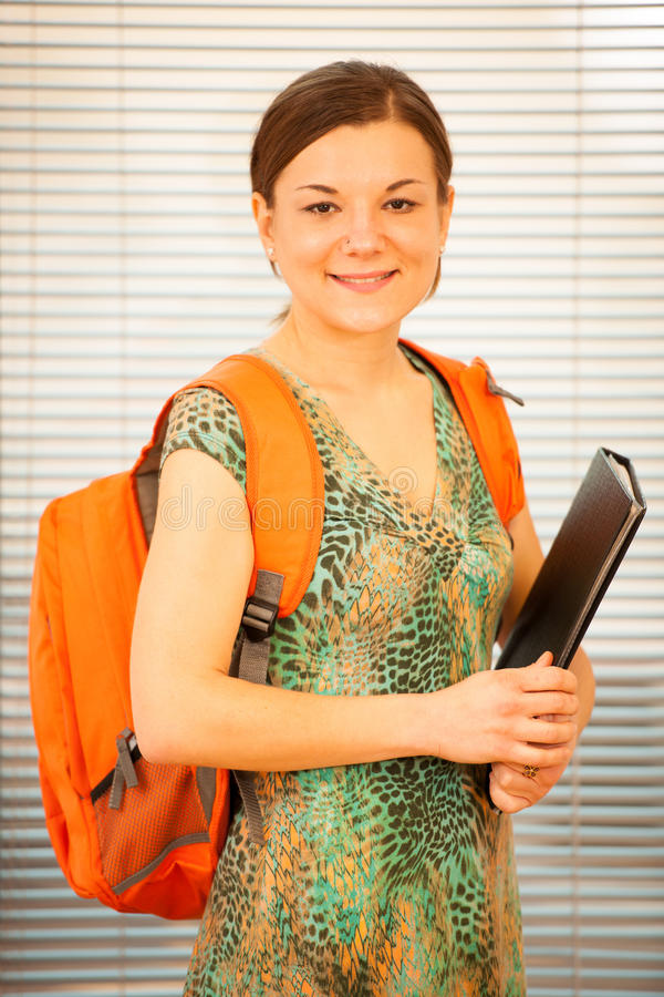 Adult woman representing lifelong learning. Woman with school ba. G smiling as a gesture of happiness and joy to study royalty free stock photos