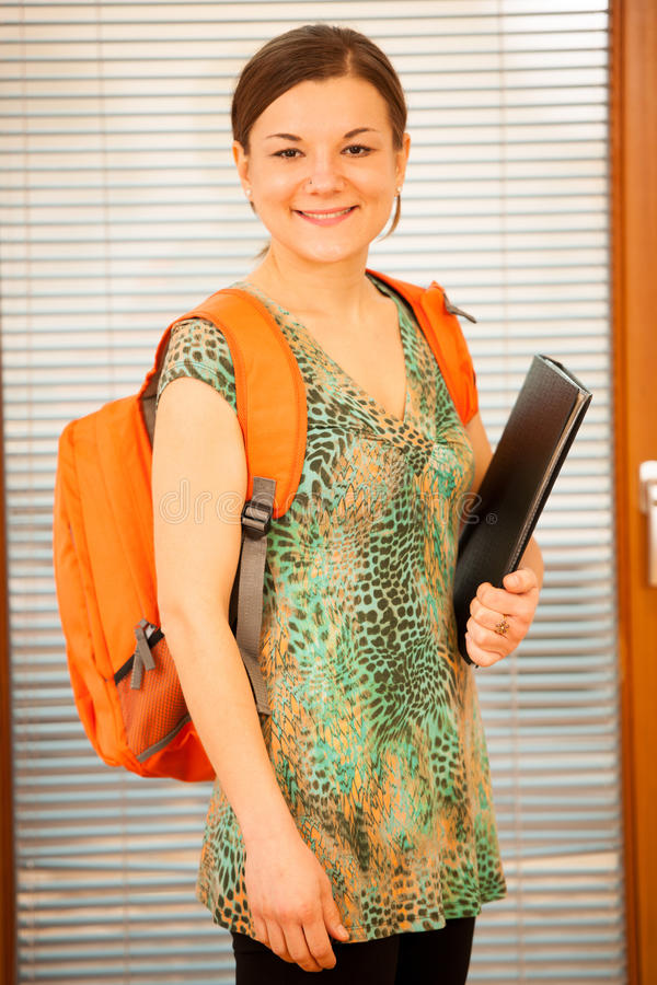 Adult woman representing lifelong learning. Woman with school ba. G smiling as a gesture of happiness and joy to study stock image