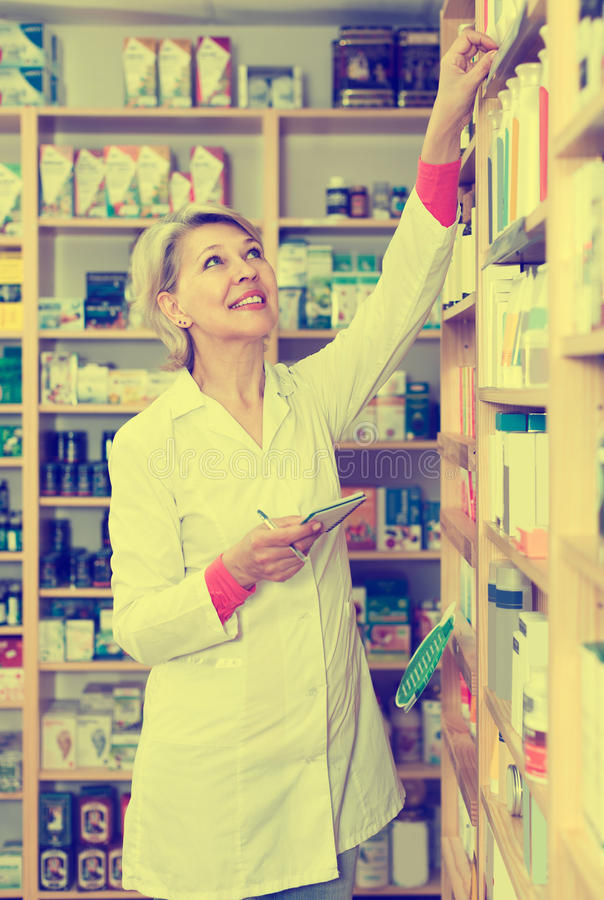 Adult woman seller writing down care products in shop. Adult woman seller writing down assortment of care products in shop stock photography