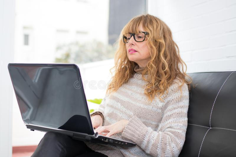 Adult woman or senior with laptop stock photo
