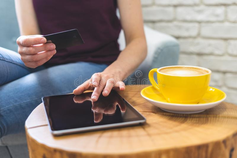 Adult woman sitting in cafe and using digital tablet and plastic card for online shopping royalty free stock image