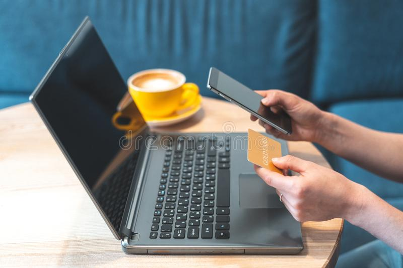 Adult woman sitting in cafe and using smartphone, laptop and credit card royalty free stock photography