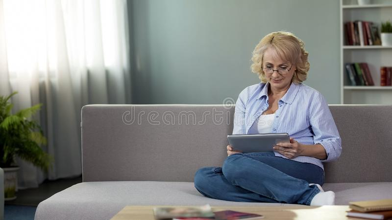 Adult woman sitting on sofa and holding tablet, buying new eyeglasses online stock photo