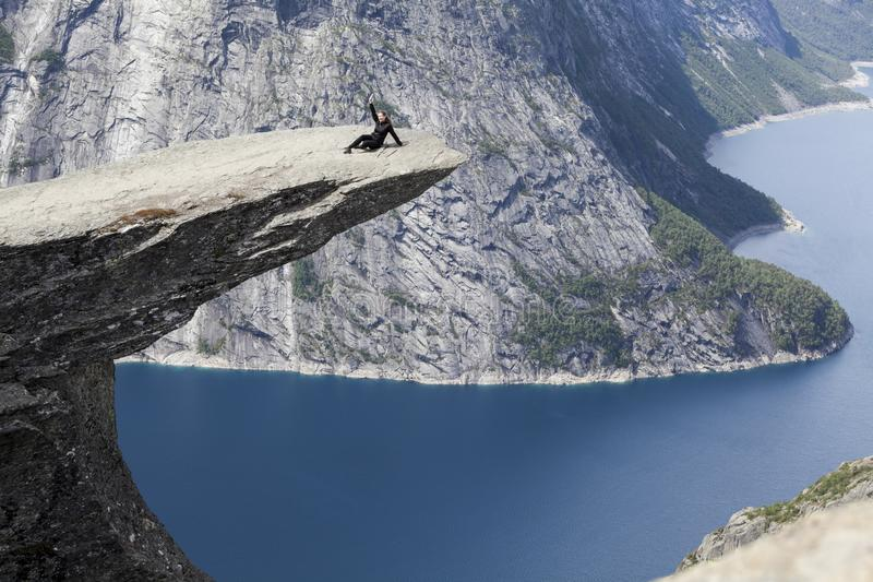 Adult woman sitting on Trolltunga rock formation and waving hand. Jutting cliff is in Odda, Hordaland county, Norway stock images
