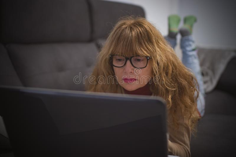 Woman on the sofa with laptop stock image