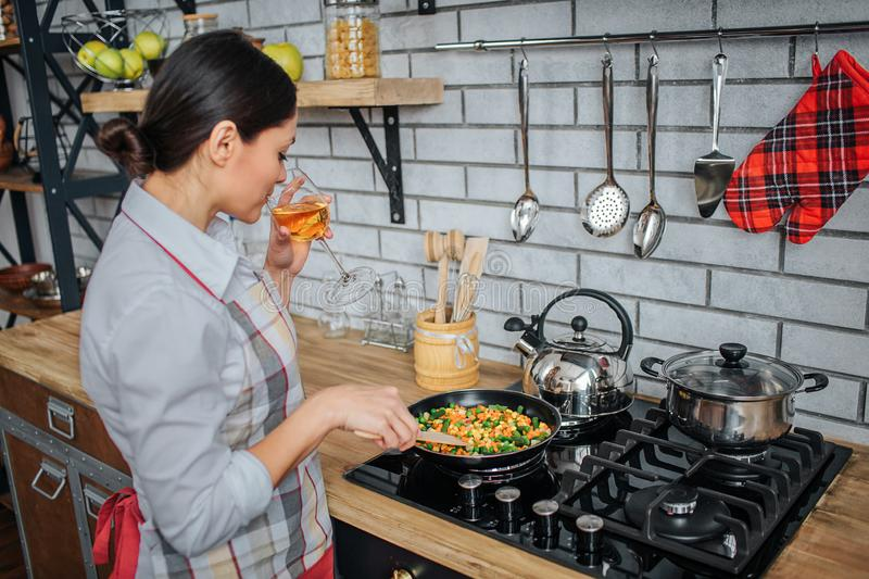 Adult woman stand at stove in kitchen. She fry food and mix it. Woman drink white wine from glass. Adult woman stand at stove in kitchen. She fry food and mix stock photos