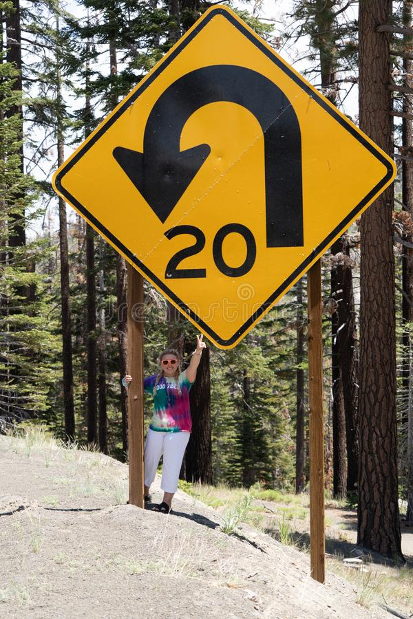 An adult woman stands next to a giant road sign in Mammoth Lakes, California, showing the scale of the size of the sign. Giving peace sign royalty free stock photography