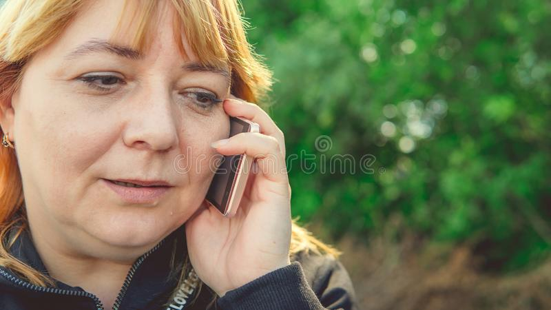 An adult woman talking on a smartphone, close-up. Female talking on mobile phone and looking away. Beautiful woman stock photo