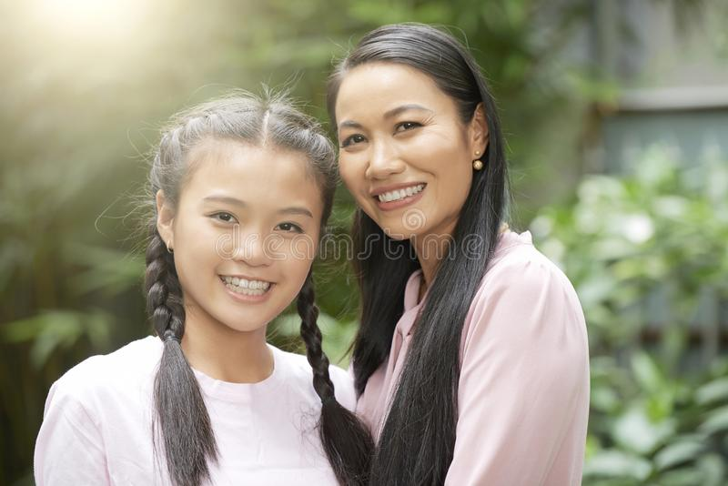Adult woman with teenage daughter. Beautiful adult Asian woman with charming teenage girl smiling at camera in sunlight stock photography