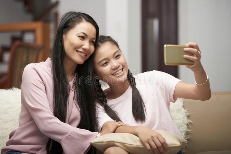 Adult woman with teenage daughter taking selfie royalty free stock photography