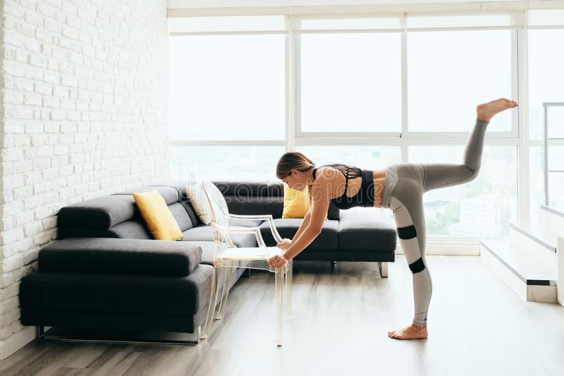 Adult Woman Training Body By Raising Legs Using Chair. Fit young Pacific Islander woman training at home. Beautiful female athlete working out for wellbeing in stock photography