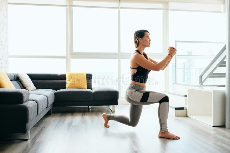 Adult Woman Training Legs Doing Inverted Lunges Exercise. Fit young Pacific Islander woman training at home. Beautiful female athlete working out for wellbeing royalty free stock image