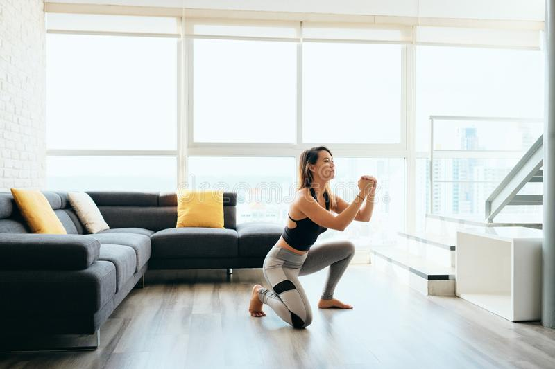 Adult Woman Training Legs Doing In and Out Squat. Fit young Pacific Islander woman training at home. Beautiful female athlete working out for wellbeing in stock photos