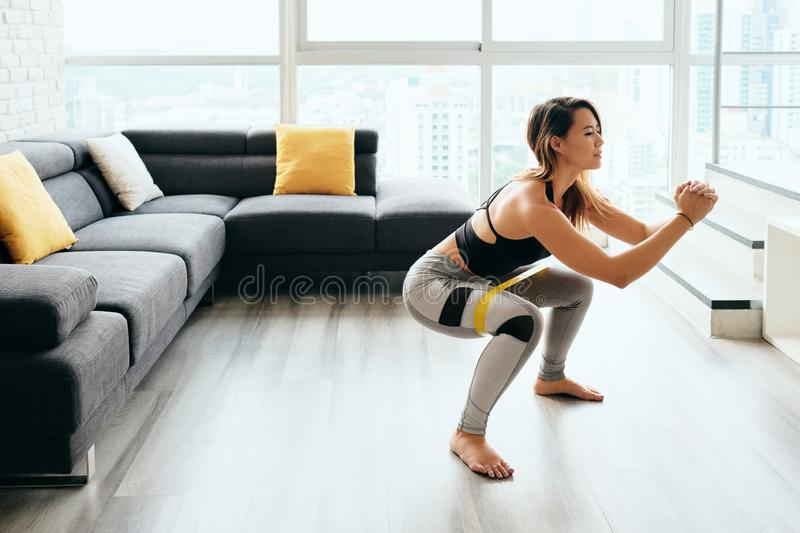 Adult Woman Training Legs Doing Side Squat at Home. Fit young Pacific Islander woman training at home. Beautiful female athlete working out for wellbeing in royalty free stock photo