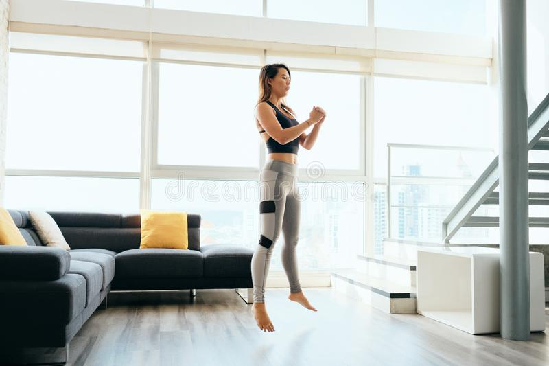 Adult Woman Training Legs Doing Squat and Jumping. Fit young Pacific Islander woman training at home. Beautiful female athlete working out for wellbeing in royalty free stock photos