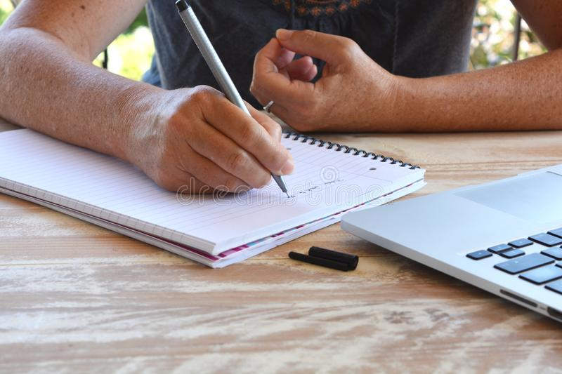 Woman writing on a notepad, close-up of pen in hand. Adult woman wearing casual summer clothes, seated at a wooden table, writing on notepad, close-up of hand royalty free stock photo