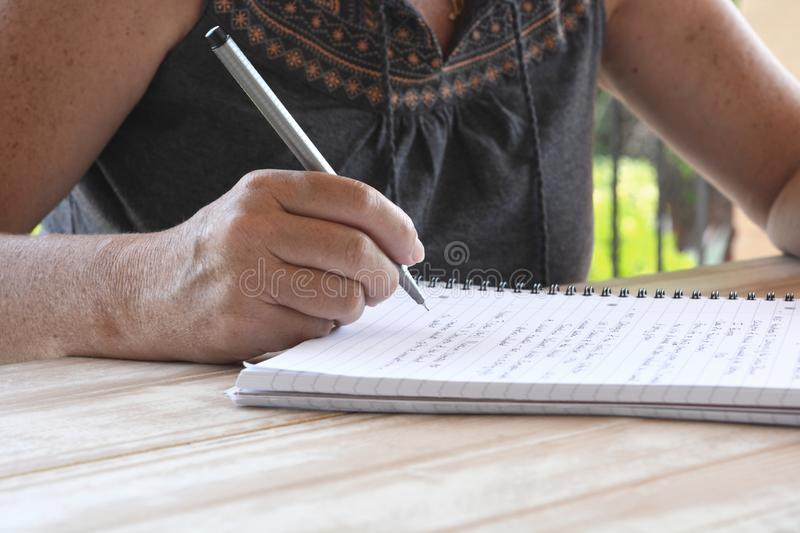 Woman writing on a notepad, close-up of pen in hand. Adult woman wearing casual summer clothes, seated at a wooden table, writing on notepad, close-up of hand stock images