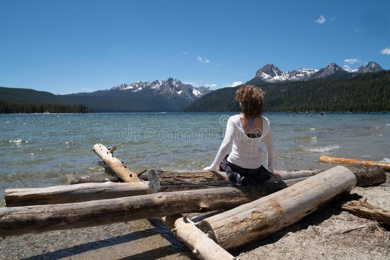 Adult woman 30-35 years sits on a pile of logs on the shoreline of Redfish Lake in Stanley Idaho in the Sawtooth Mountains in royalty free stock images