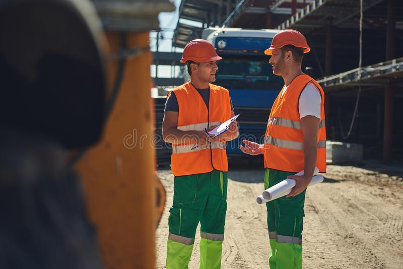 Adult workers in helmets are standing outdoors stock photography