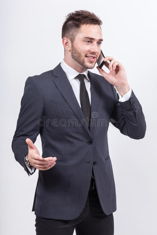 Picture of serious businessman standing with cellphone stock photography