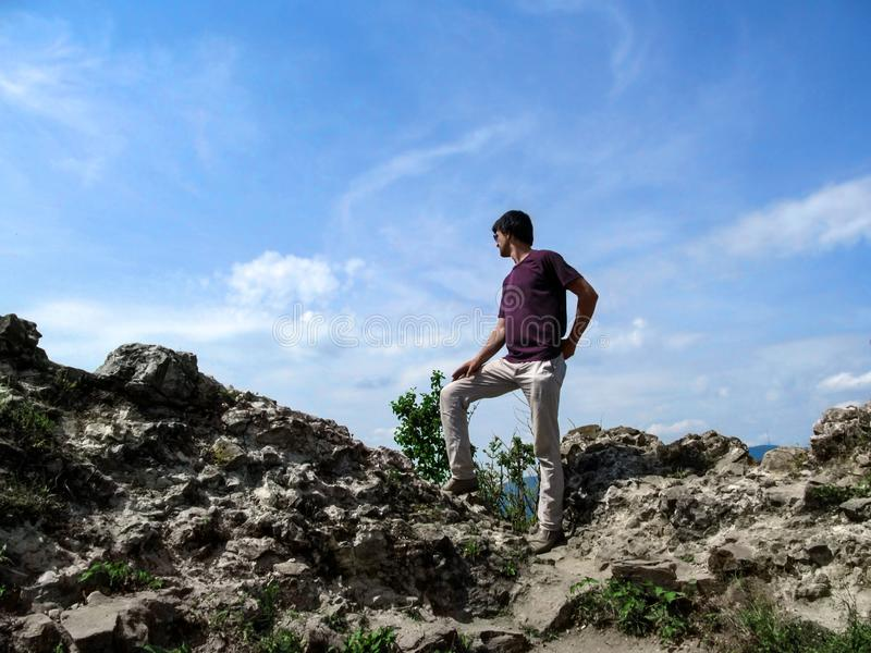 The adult young man climbed a rock and looks into the distance in a winner pose. Dark-haired slim guy in a T-shirt, white pants royalty free stock photos