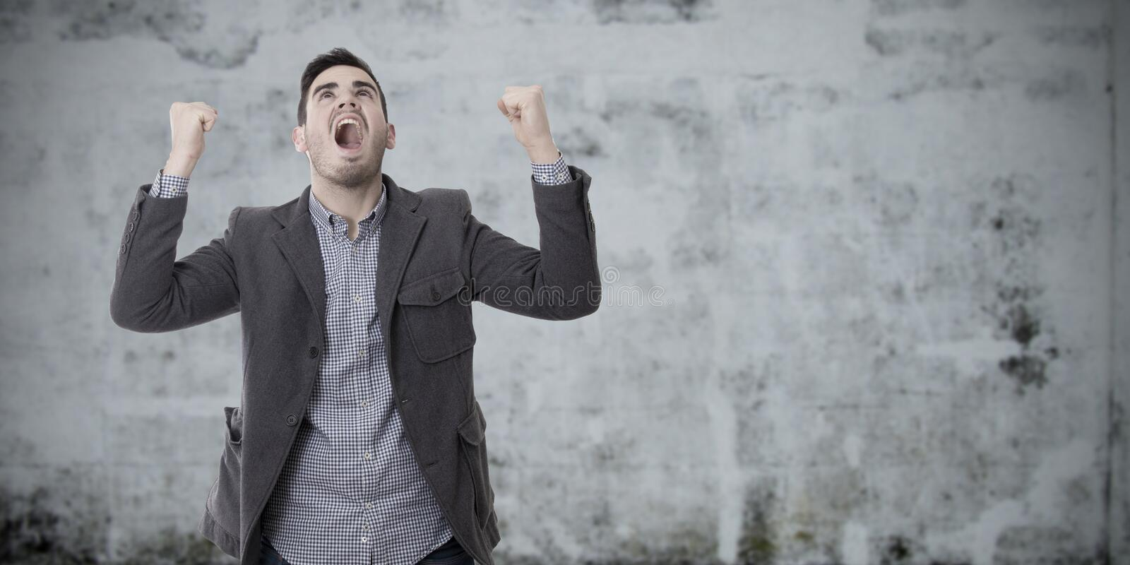 Man shouting enraged with the arms raised. Adult young man shouting enraged with the arms raised royalty free stock photography