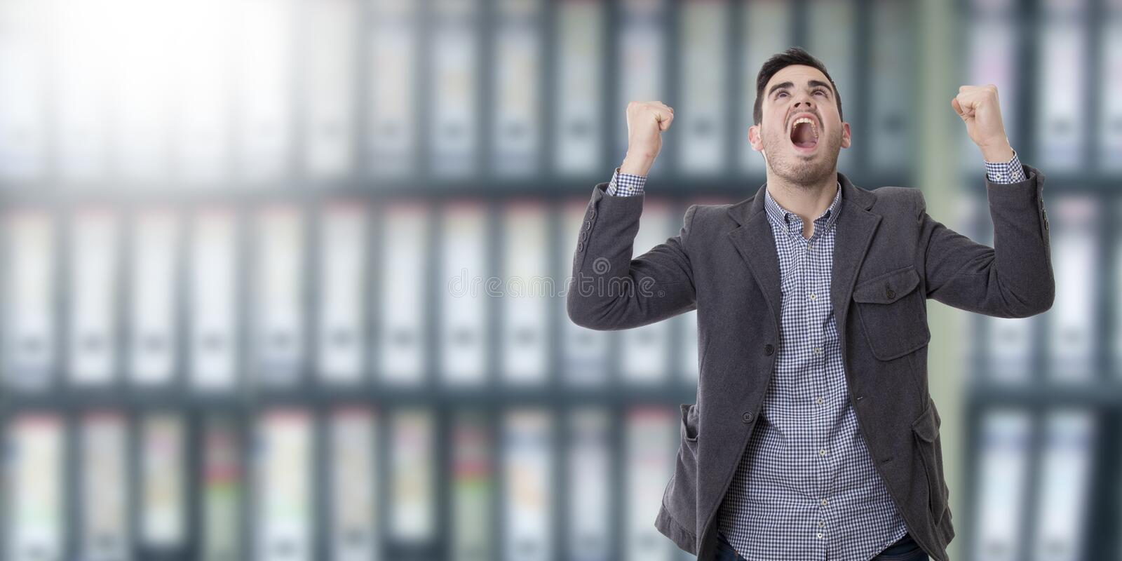 Man shouting enraged with the arms raised. Adult young man shouting enraged with the arms raised royalty free stock photo
